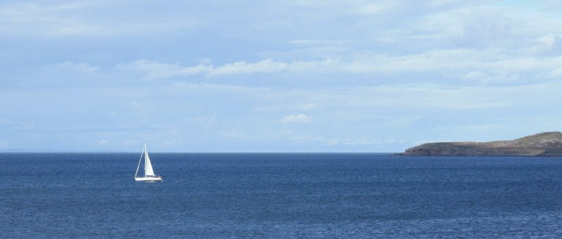 Image of a yacht sailing off a headland
